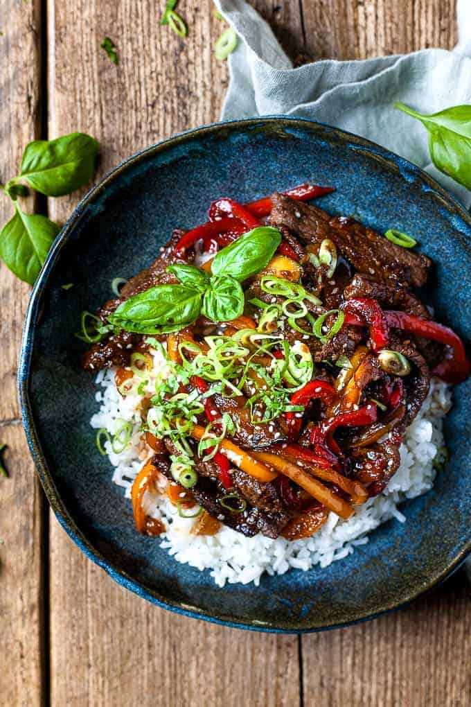 Ginger beef stir fry over rice in a blue bowl with a napkin and chop sticks.
