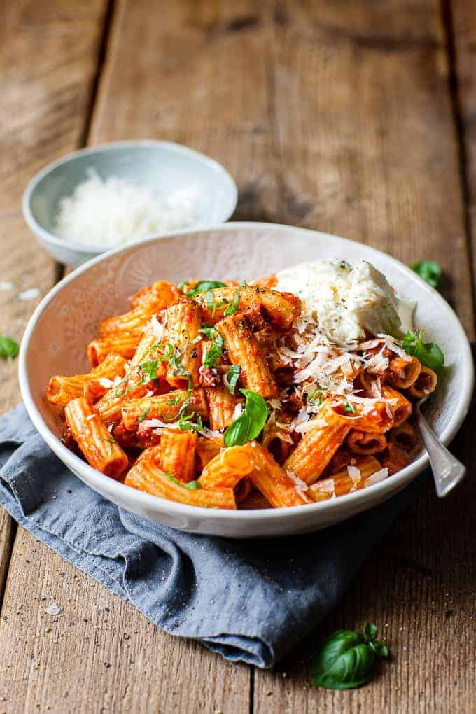 Chorizo pasta using only Aldi ingredients in a white bowl on a wood table.