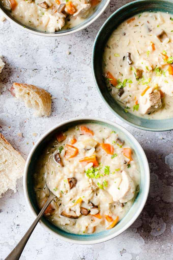 Three bowls of Chicken and Rice soup on a white table with Bread.