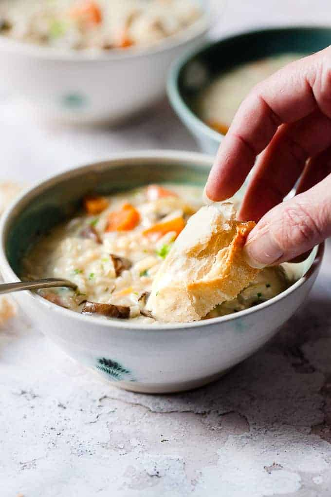 Chicken rice soup recipe in a bowl with bread.