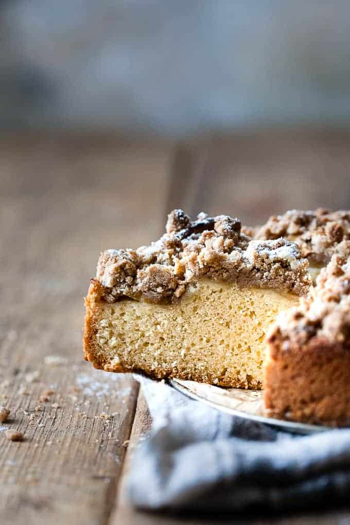 Slice of apple crumb cake on a wooden table.