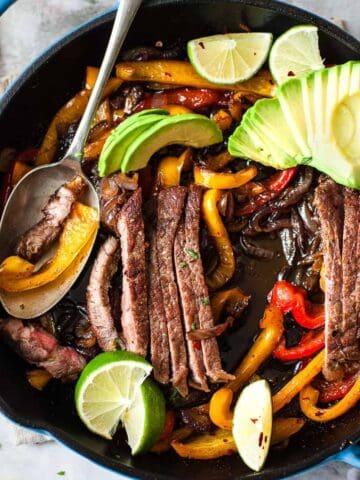 Seared steak fajitas in a skillet made using Aldi ingredients.