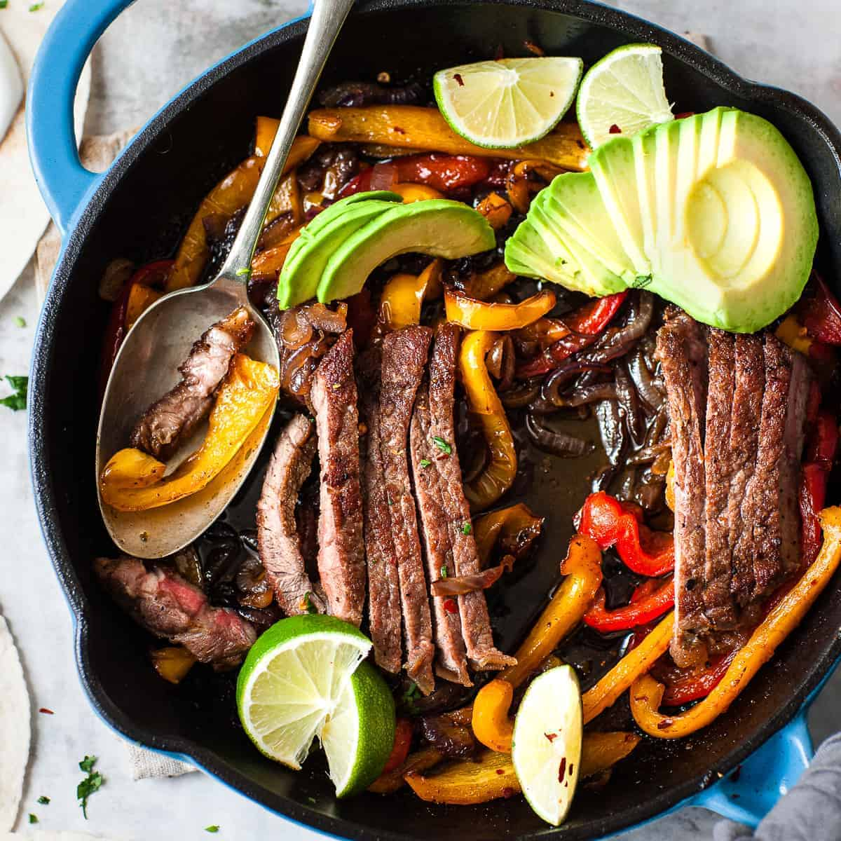 Seared steak fajitas in a skillet made using Aldi ingredients.