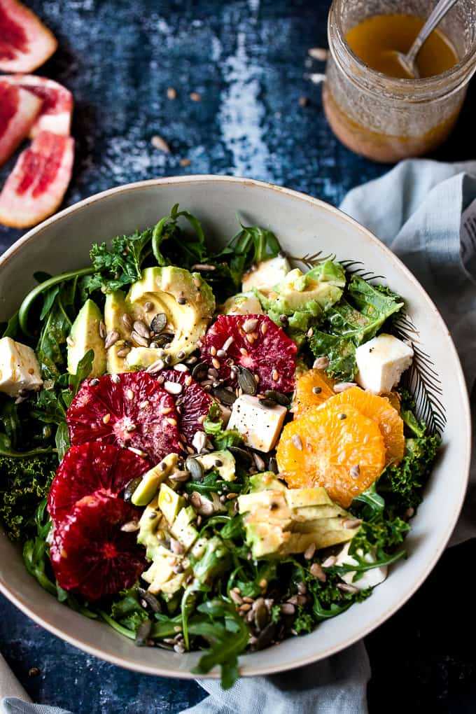 Massaged citrus kale salad in a bowl with cheese and dressing.