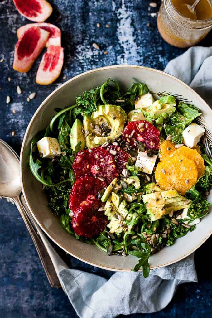 Kale salad with avocado and oranges on a blue table