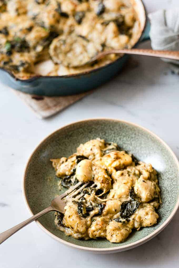 Spinach and artichoke gnocchi in a bowl with cheese. All ingredients from Aldi.