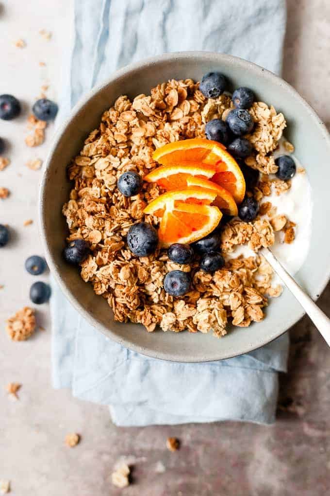 bowl of maple granola with a spoon on a blue napkin