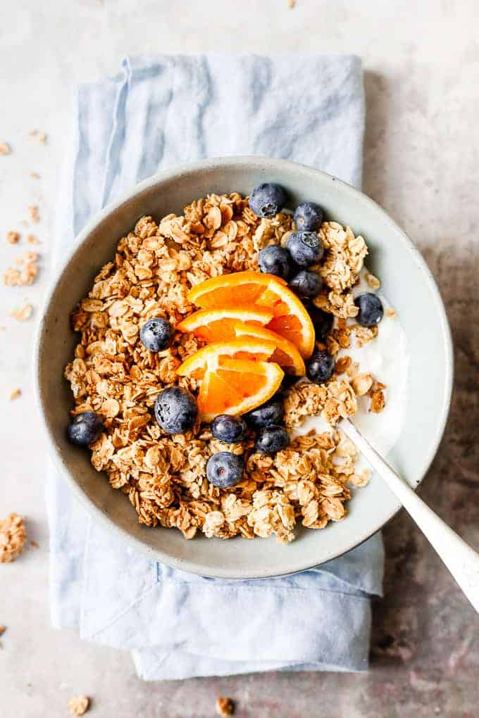 chunky granola with fresh fruit on a blue table