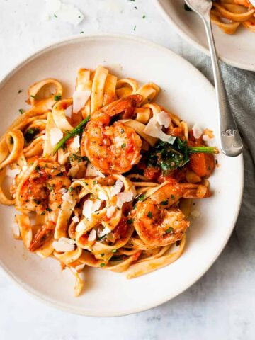 Prawn pasta in a white bowl with spinach and tomato sauce.