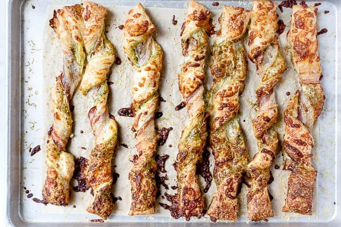 Puff pastry and bacon cheese straws on a baking tray.