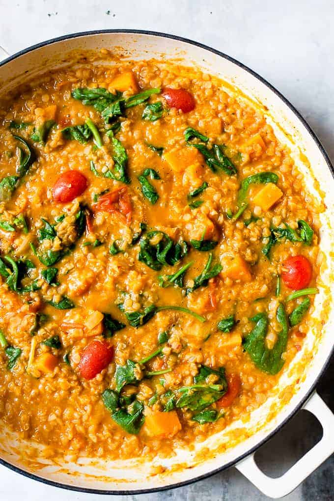 Red lentil dhal curry in a white pan on a grey table with spinach and tomatoes.