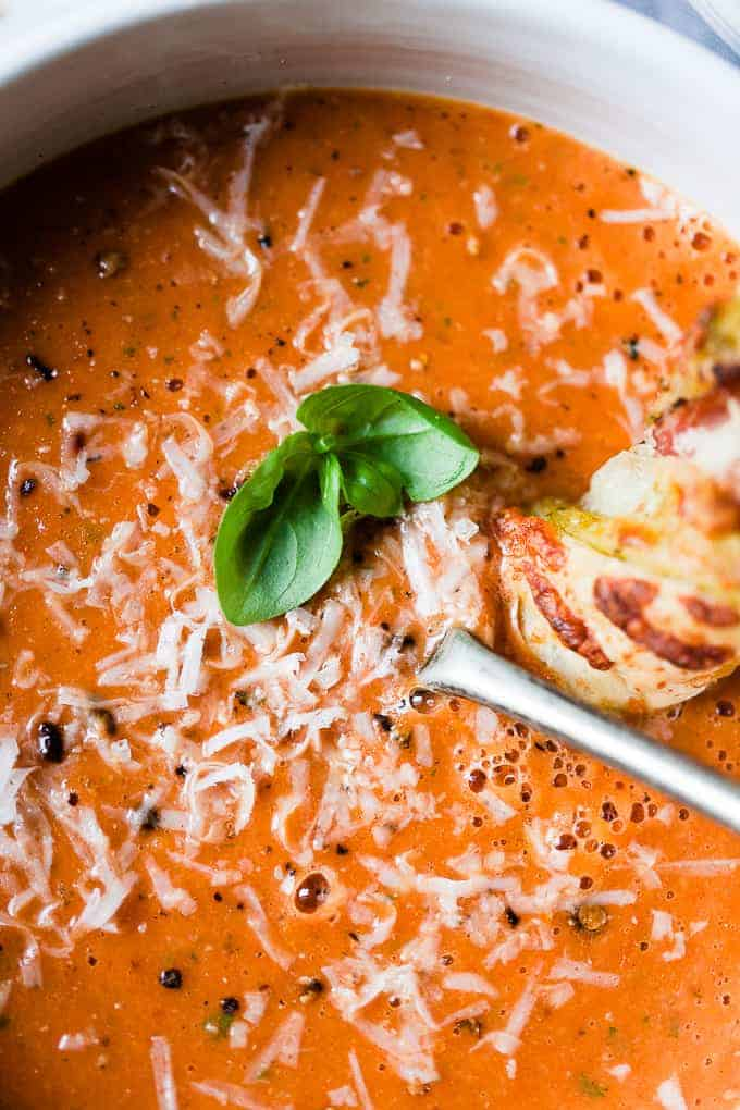 Oven roasted tomato soup in a bowl with parmesan cheese on top.