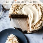 Walnut coffee cake with text overlay on a cake plate. Aldi ingredients.