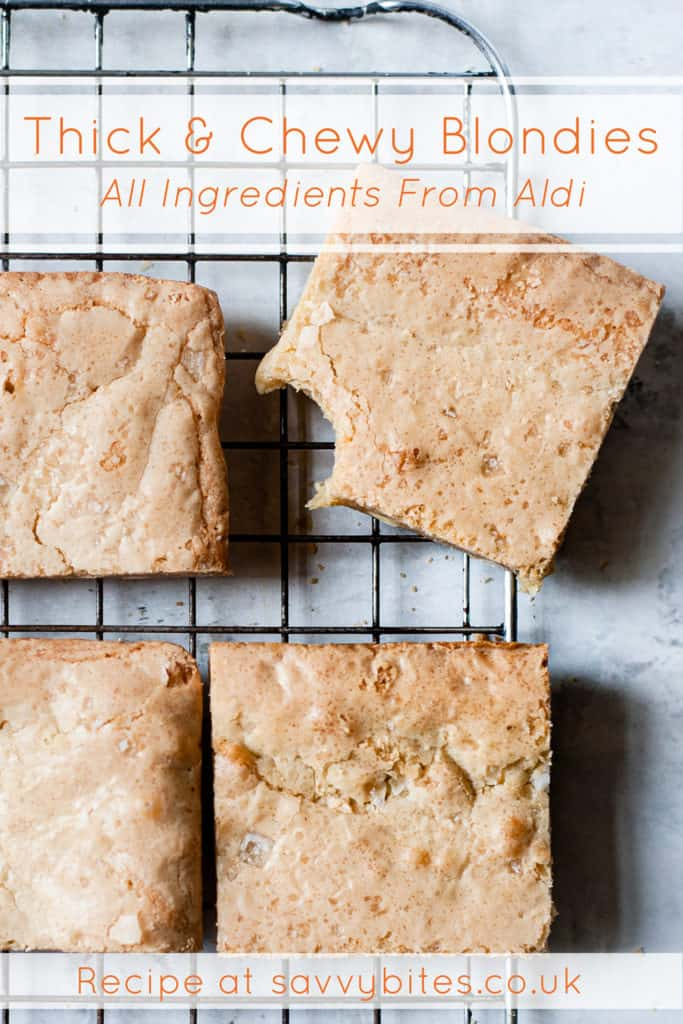 Thick and chewy blondies on a cooling rack. One bowl white chocolate.