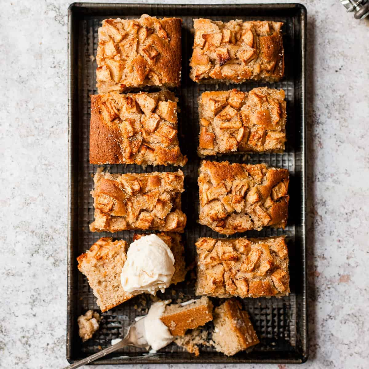 Apple cake in slices on a baking tray with ice cream.