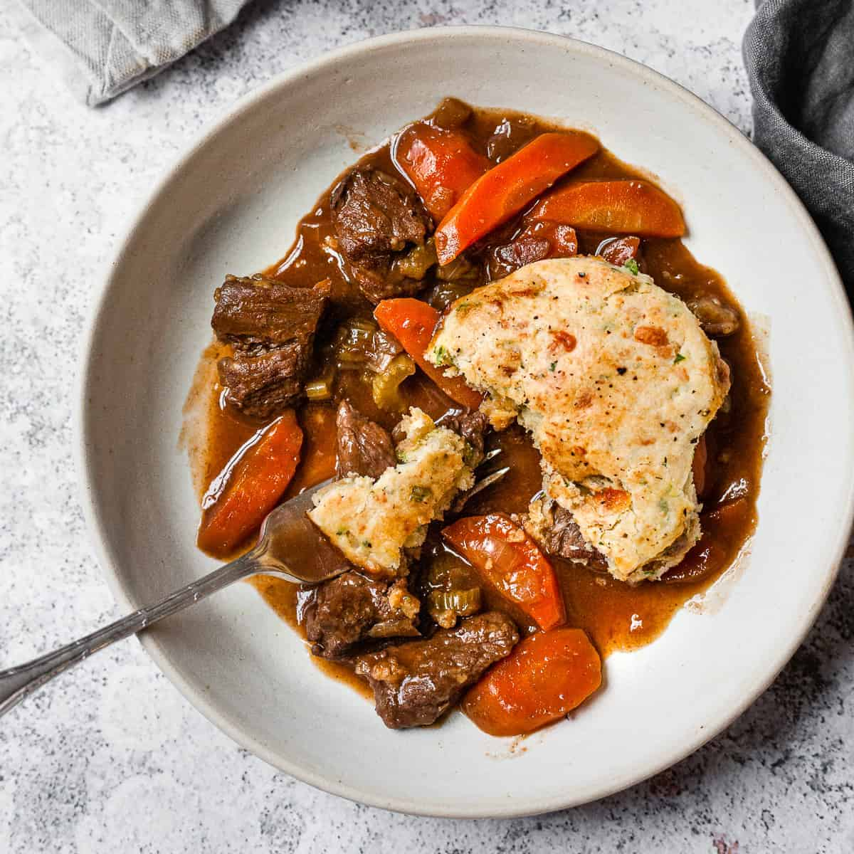 beef cobbler in a bowl with cheese scones.