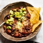 slow cooker chilli in a bowl with tortilla chips.