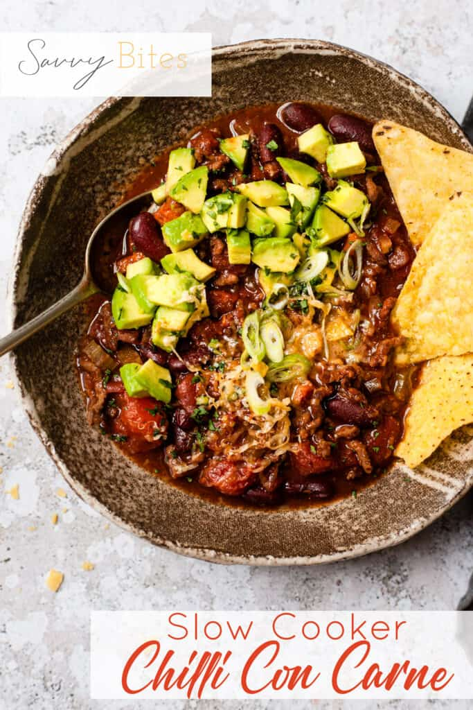 slow cooker chilli in a bowl with tortilla chips. Text overlay.