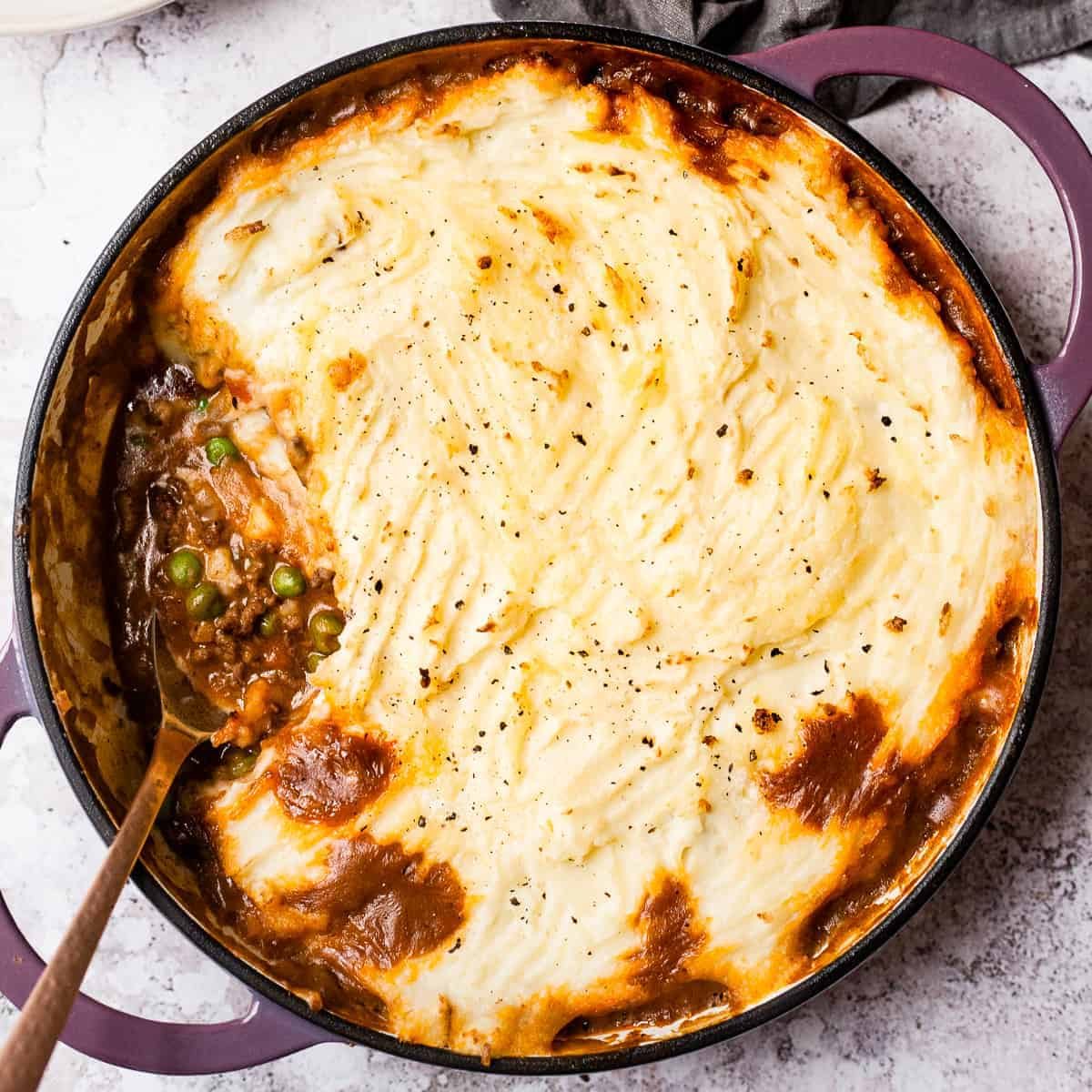 Cottage pie with a spoon in it and a napkin.