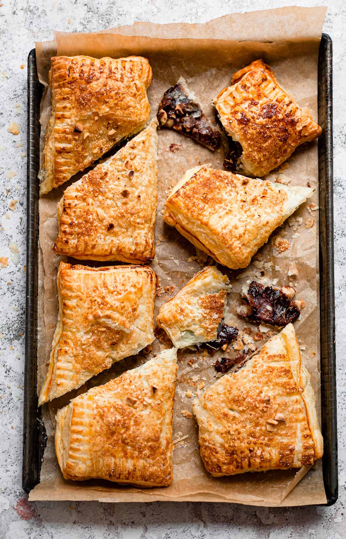 Nutella puff pastries on a baking tray with baking paper.