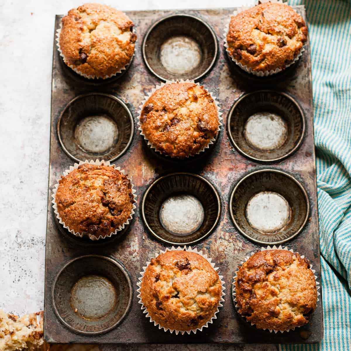 Muffins in a baking tin with a blue tea towel
