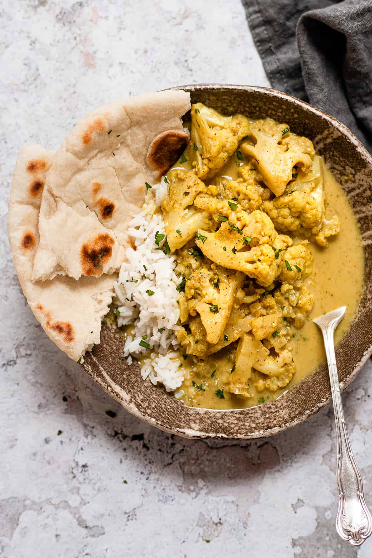 Cauliflower curry in a brown bowl with rice