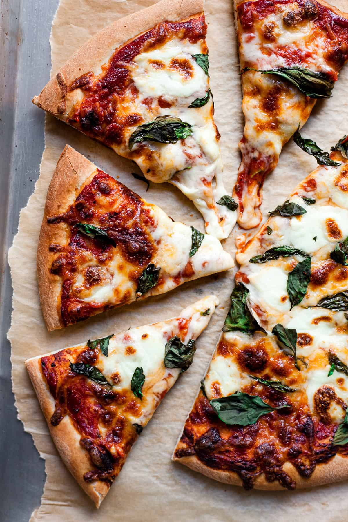 Margherita pizza slices on a piece of baking paper.