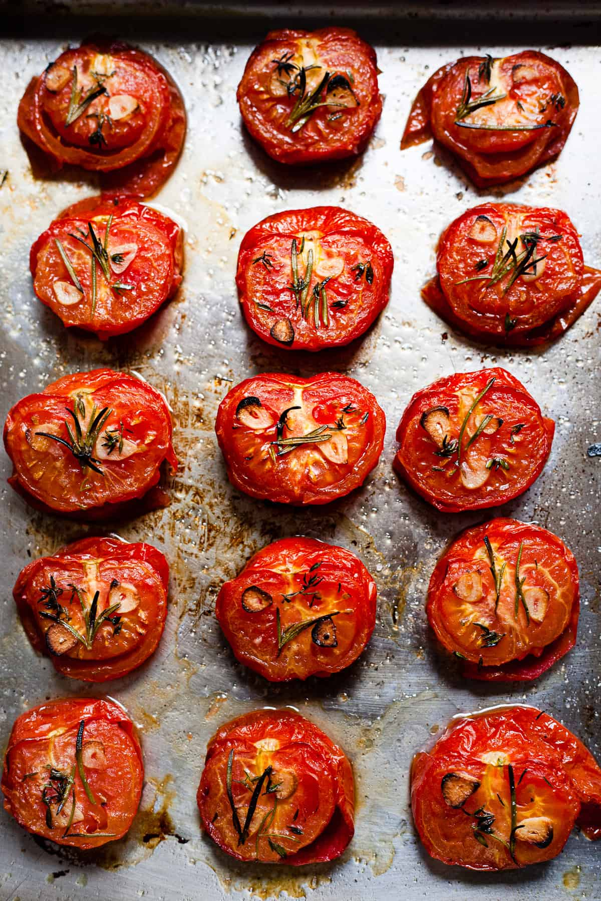 roasted tomatoes on a baking tray with herbs
