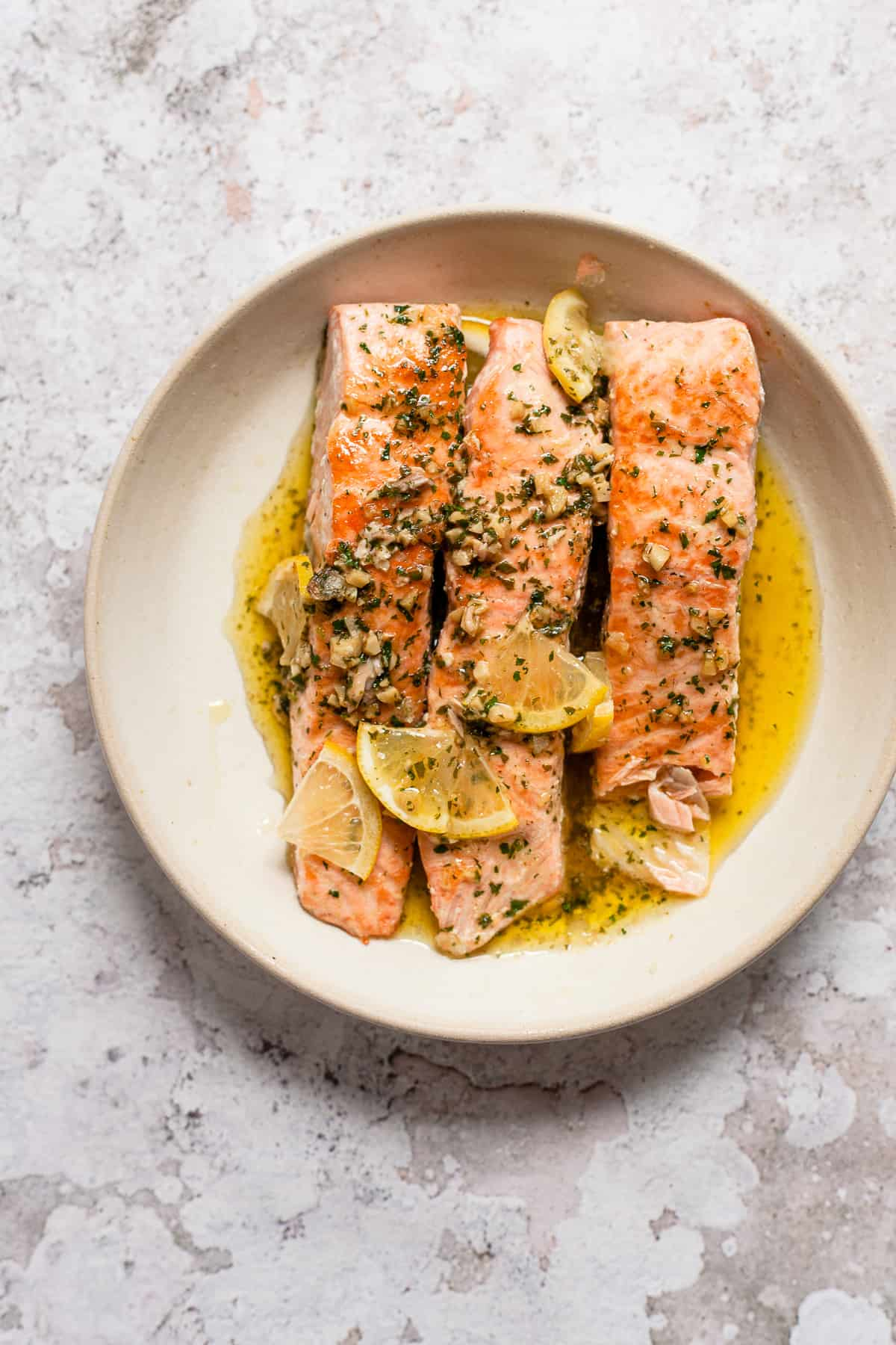 Salmon fillets with slices of lemon and garlic butter.