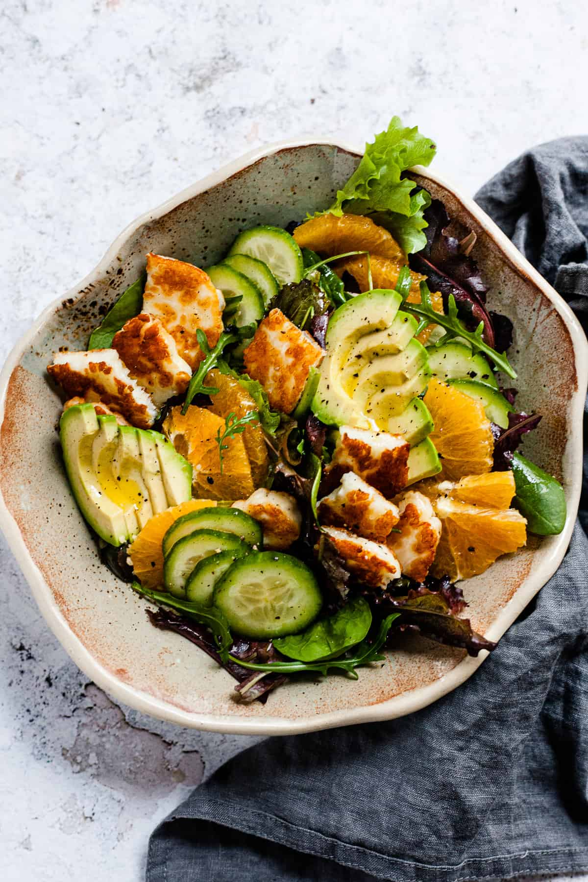 pan-fried halloumi salad in a bowl on a white table.
