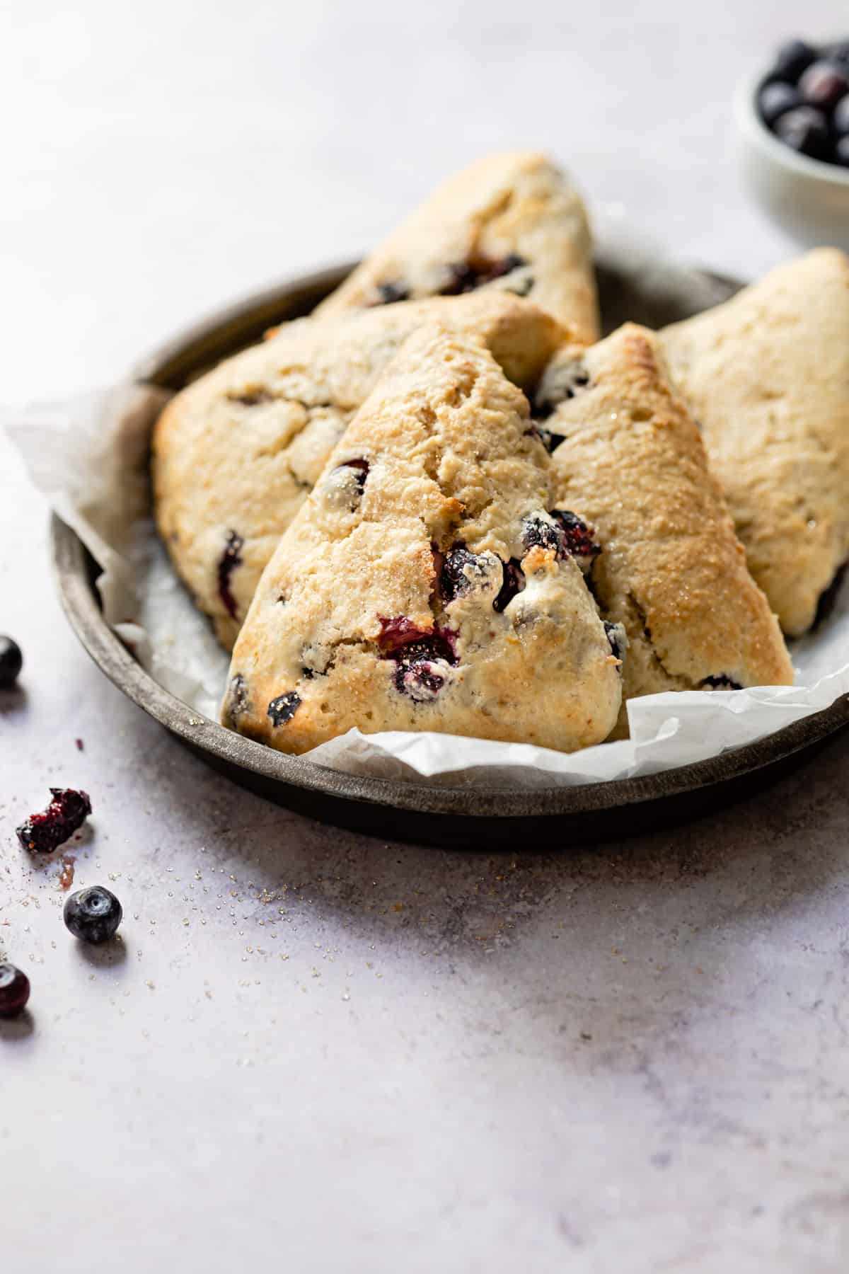 Blueberry scones in a tin on a white table