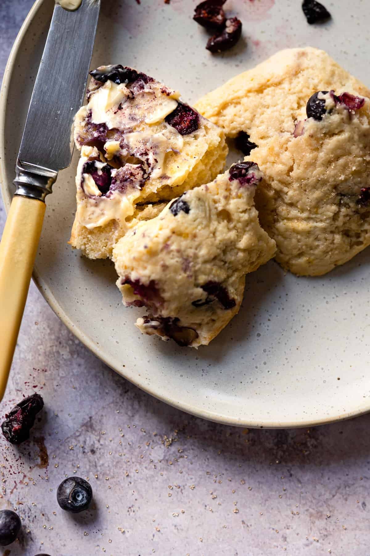 Blueberry scone with butter on it.