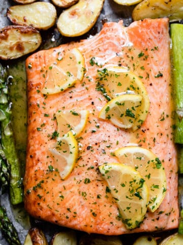 baked salmon with honey garlic butter sauce and lemons on a baking tray