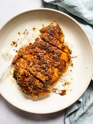 brown sugar pork chops on a white plate with a fork