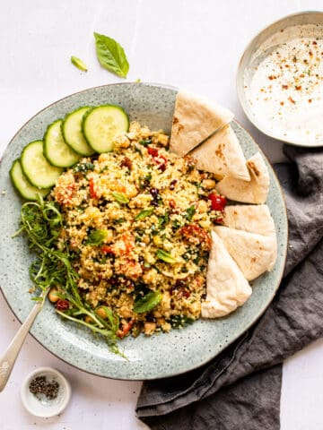 Moroccan couscous in a blue bowl with pita bread