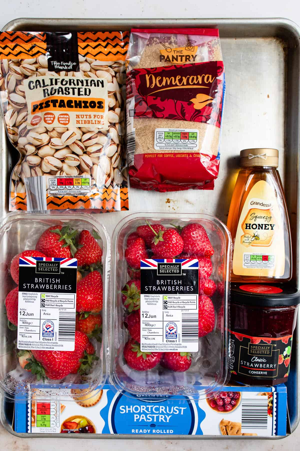 Aldi ingredients for fresh strawberry tart on a baking tray.