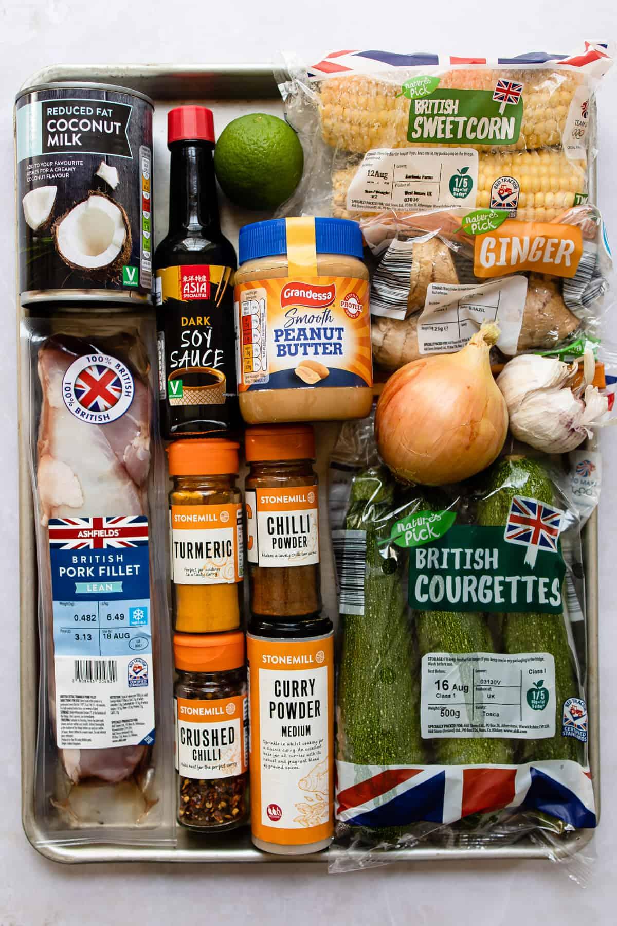 Aldi ingredients for pork curry on a baking tray.