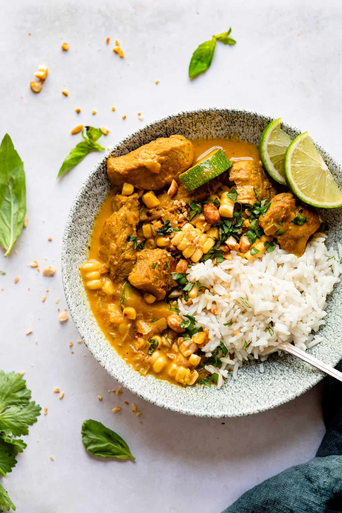 Pork curry in a blue bowl with rice and basil.