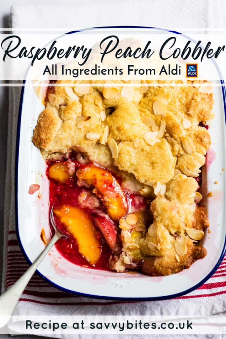 peach raspberry cobbler in a baking dish with a spoon.