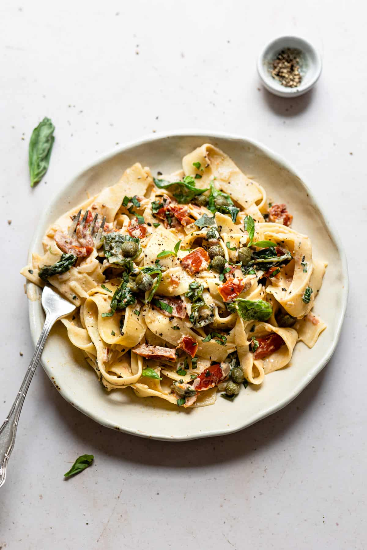 Sundried tomato pasta on a white plate with a fork.- Aldi recipes